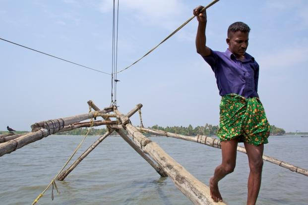 A fisherman walking on a Chinese fishing net.