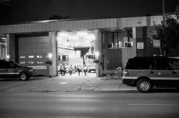 Firefighters sitting under an open garage door at night
